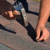 Roofing Contractor Laying Asphalt Shingles. House Roofing