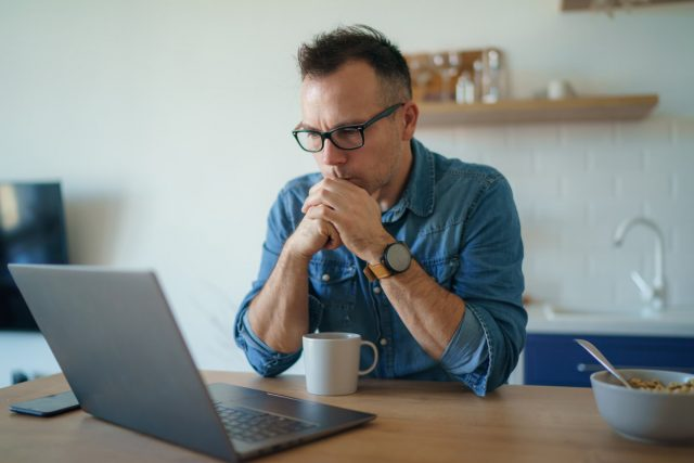 man looking at computer to review the facts about roofing insurance