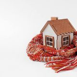 small house wrapped in scarf following home winterization checklist